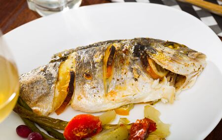 Appetizing roasted dorada served with baked asparagus, tomatoes and onion garnished with cranberries