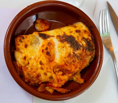 Italian meat lasagna in a clay plate