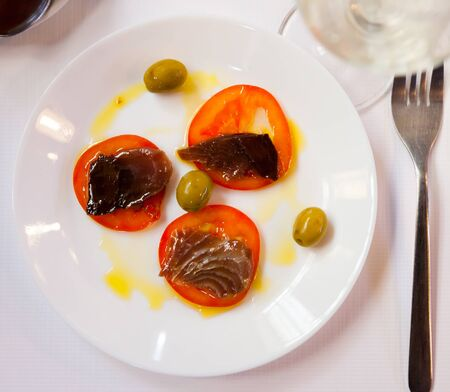 Top view of delicious andalusian tapa of fresh sliced sarda served with tomato, sauce and green olives on white plate