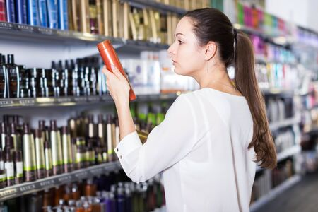 Serious young woman attentively choosing hair products at cosmetics  shop