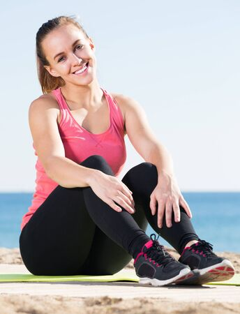 Beautiful young sporty woman exercising at sea beach