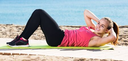 Young positive woman doing yoga at seaside on a sunny day