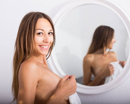 smiling sensual nude woman with long hair standing in bedroom 写真素材