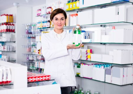 Female is showing body care products in pharmacy. Stockfoto