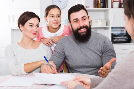 Young parents signing papers for new house with their daughter Stock fotó - 133818367