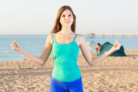 Female 20-25 years old is standing and practicing meditation in blue T-shirt on the beach.