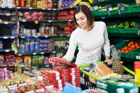 Smiling female shopper searching for sweets in supermarket Banco de Imagens