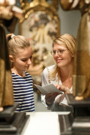 Girl with woman in glasses looking with interest at ancient sculptures in museum, using guidebook Banque d'images