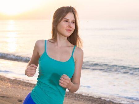 Sportswoman is jogging on the beach near the ocean. Stock Photo - 134050592