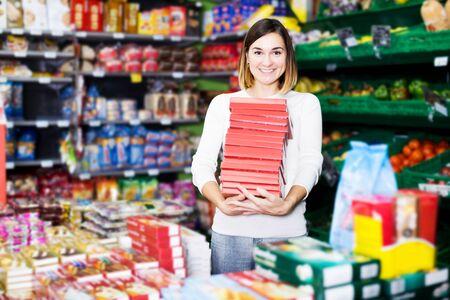 Happy young woman choosing delicious sweets in supermarket Banco de Imagens