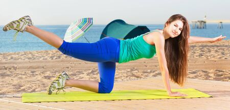 Young happy  woman in blue T-shirt is practicing stretching on the beach. 스톡 콘텐츠