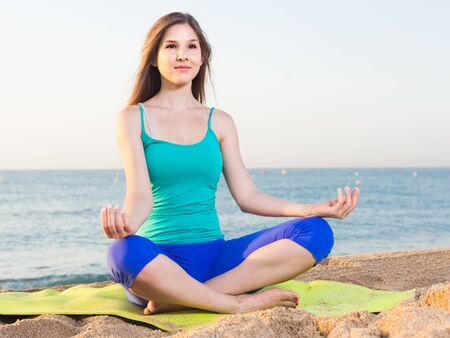 Female 20-25 years old is sitting and practicing meditation in blue T-shirt on the beach. Stock Photo