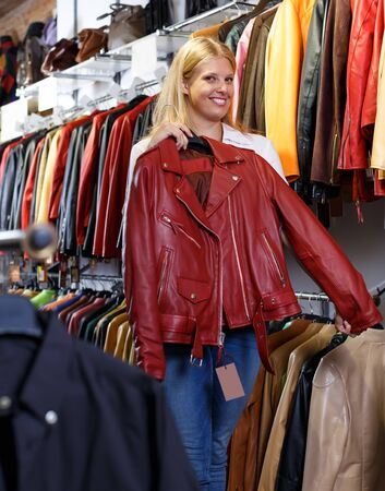 Portrait of smiling female customer with leather jackets in clothes store