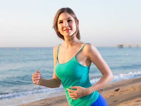 Sportswoman is jogging on the beach near the ocean.