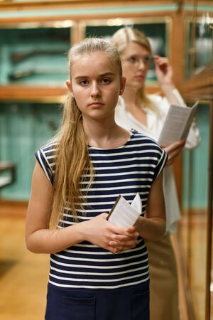 Portrait of girl holding guidebook in museum of art, mother on background