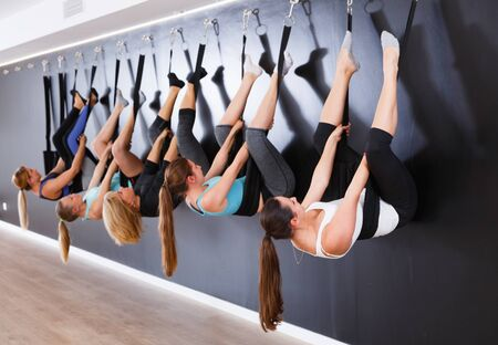 Young women exercising yoga wall on straps in fitness center