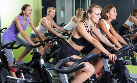 Athletic cheerful  girls during workout on stationary bicycle in fitness gym Stock Photo - 134050645
