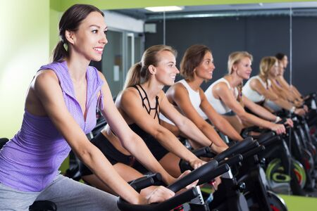 Young athletic women cycling on stationary bike in fitness center Stock Photo - 134050646