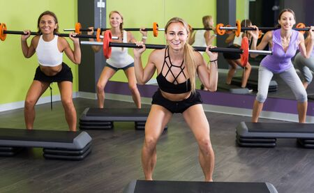 Smiling english athletic girls during workout in gym with barbell Stock Photo
