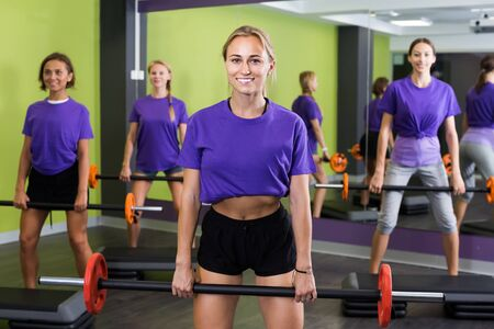 Team of fitness girls in identical blue T-shirts performing deadlift exercise with bars Stock Photo - 134050654