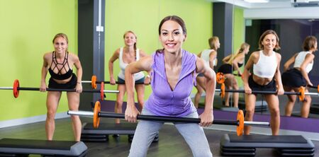 Portrait of happy smiling cheerful sporty women exercising with barbell in fitness club Stock Photo - 134050651