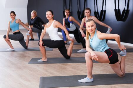Young sporty women practicing yoga positions during training at gym Stock Photo - 134050652