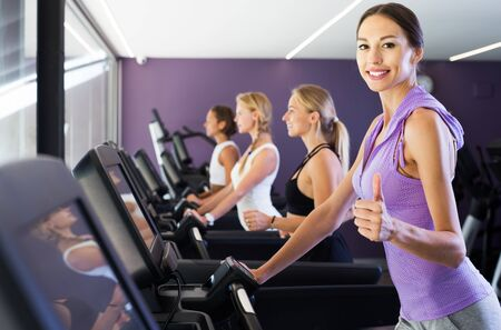 Smiling sporty girls running on treadmill in fitness club giving thumbs up