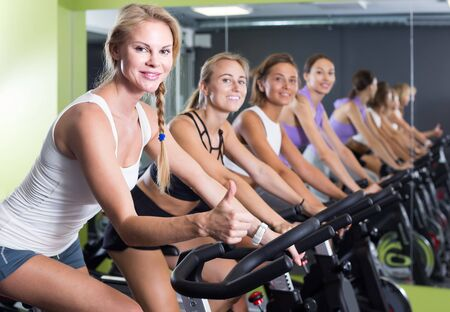 Portrait of happy european women on exercise bike gesturing thumbs up at gym Stock Photo