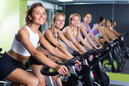 Athletic cheerful young girls during workout on stationary bicycle in fitness gym