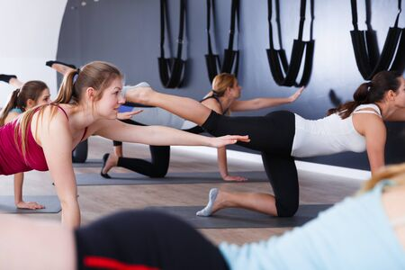 Group of young females exercising during yoga class at gym