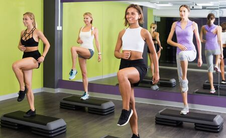 Young positive spanish  fit females working out  with step platforms in gym Stock Photo