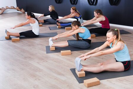 Group of young  cheerful   females exercising during yoga class at gym