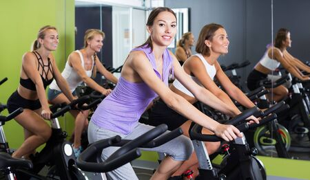 Young smiling sporty women cycling on stationary bike in fitness club