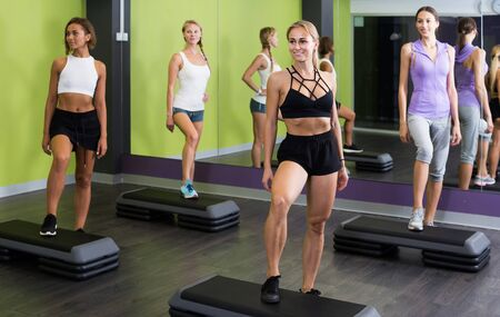 Portrait of young germany fit woman performing step aerobics in fitness club