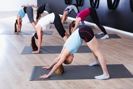 Group of young glad cheerful positive  females exercising during yoga class at gym Stock Photo