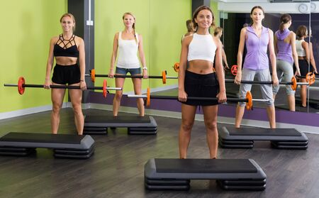 Group of young women training with barbell workout at fitness center Stock Photo - 134050679