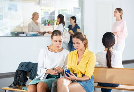 Female students talking and using smartphones, spending time together during recess between lectures in hall