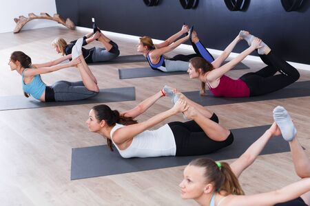 Group of sporty girls practicing various yoga positions during training indoors Stock Photo - 134050692