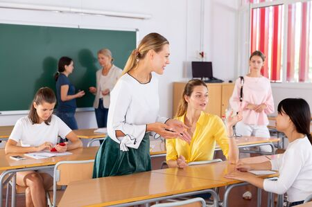 Group of smiling students with teacher chatting in break between lessons indoors