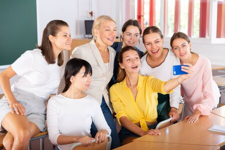 Cheerful female students with woman teacher making selfie in auditorium