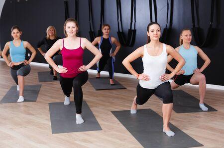 Smiling young women training yoga positions in modern yoga studio Stock Photo