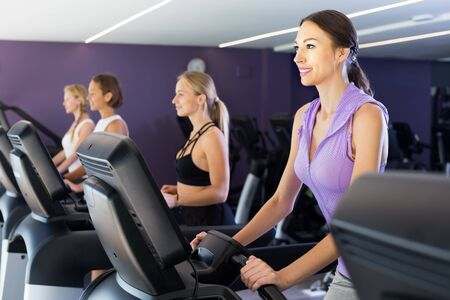 Young sporty women in gym clothing running on treadmill in fitness center Stock Photo - 134050713