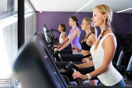 Four fit women running on treadmills in modern fitness center Stock Photo - 134050717