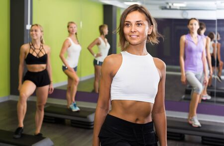 Portrait of young american fit woman performing step aerobics in fitness club