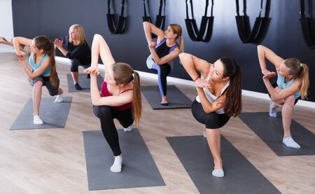 Group of sporty girls practicing various yoga positions during training indoors Stock Photo - 134050722