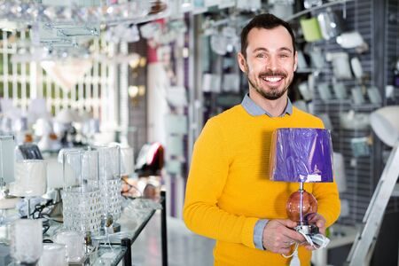 Young  cheerful positive man in shop of home appliances choosing modern and stylish lamp for home interior