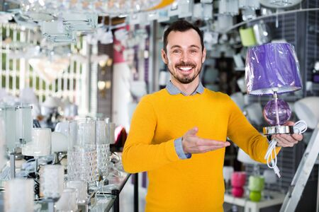 Young happy cheerful man in shop of home appliances choosing modern and stylish lamp for home interior