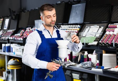 Glad friendly confident auto mechanic of car painting workshop pouring paints in paint-spray gun