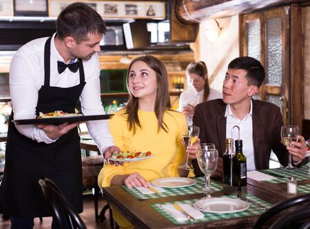Man waiter is brings order to couple who have dinner and drink wine in restaurant. Zdjęcie Seryjne