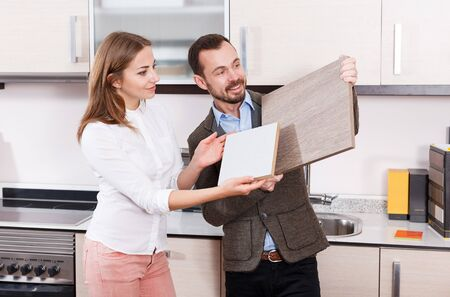Loving couple choosing kitchen furniture materials for their apartment
